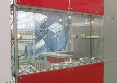 Parede de estande com vitrine embutida montada com perfis de alumínio da linha Maxxi e fixadores tipo spider linha F2000