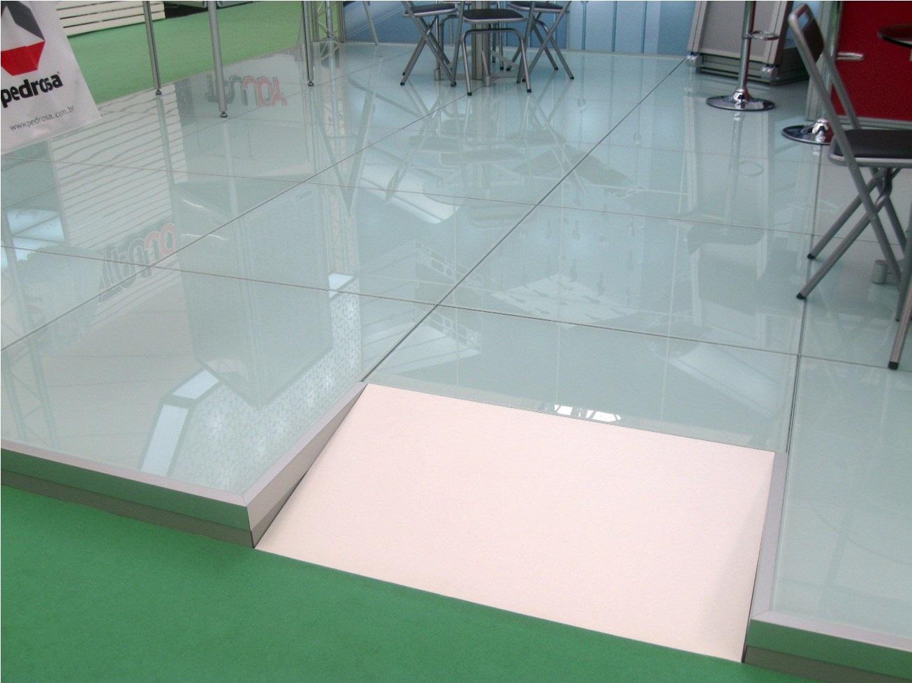 Piso elevado com vidro adesivado em estrutura montada com perfis de alumínio com regulagem de altura e com rampa de acesso. Ideal para stands, lojas, quiosques em shopping e aeroportos e outros ambientes comerciais.